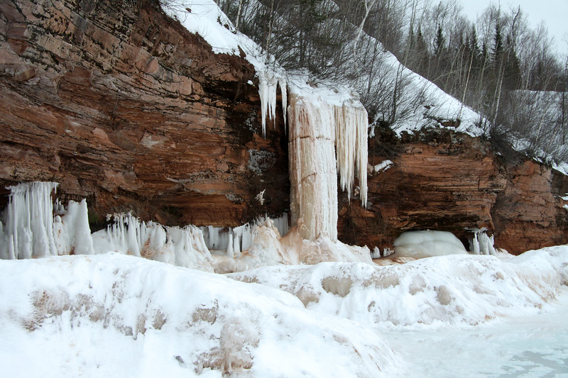 Fragmented ice stream/waterfall meets the ice waves of Lake Superior at the sedimentary sandstone cliff.