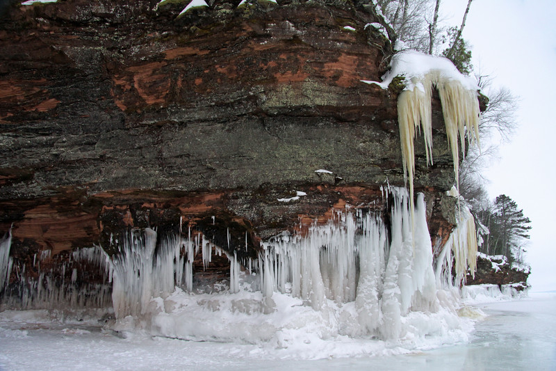 Sandstone sea cave wall, coated with lichen, iron oxide icicles, and wave ice.