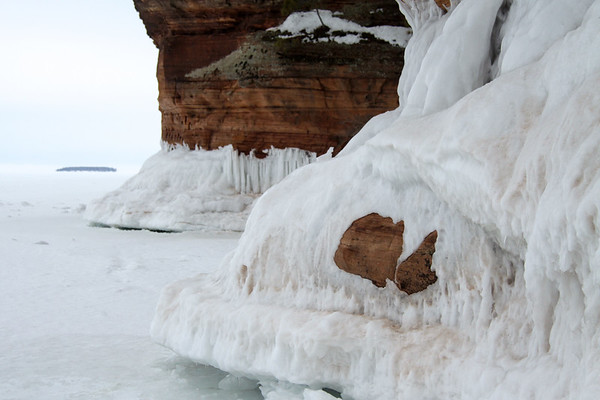 Sandstone rock shoreline protruding thru the Lake Superior wave ice - with Eagle Island (landing not permitted upon this bird sanctuary) about 2 mi. (3 km) off-shore from the Bayfield Peninsula shoreline.  Eagle Island is the western most and 2nd smallest (about 28 acres) of the 21 Apostle Islands.