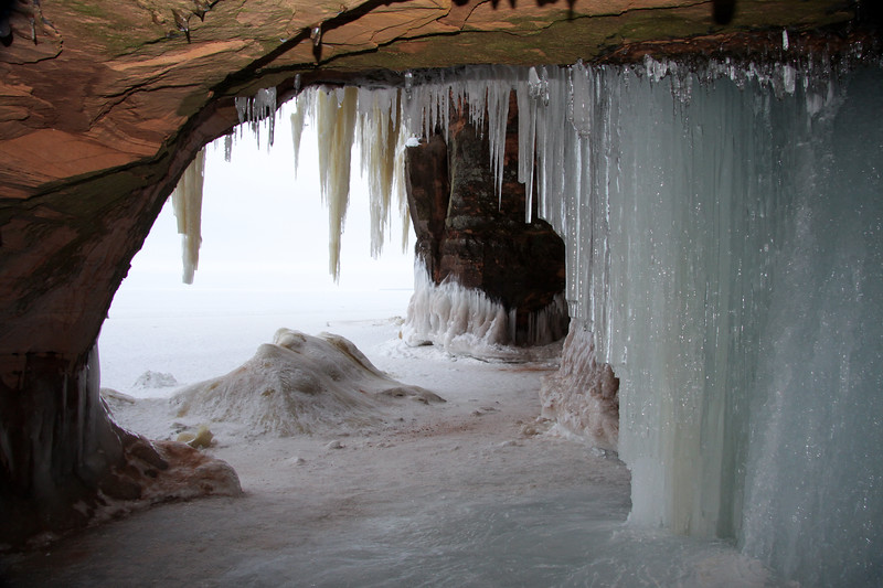 Glistening spring water ice from inside a sandstone sea/ice cave.