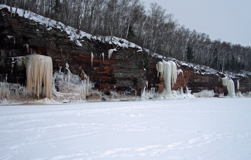 Frozen streams/waterfalls meets the frozen waves of Lake Superior, along the sedimentary sandstone cliffs, lined with aspens, white birch, and white pines.