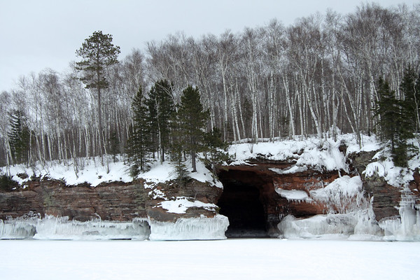 "Eroded sea cave (known as the ""garage"") along the rocky shoreline of the Bayfield Peninsula."