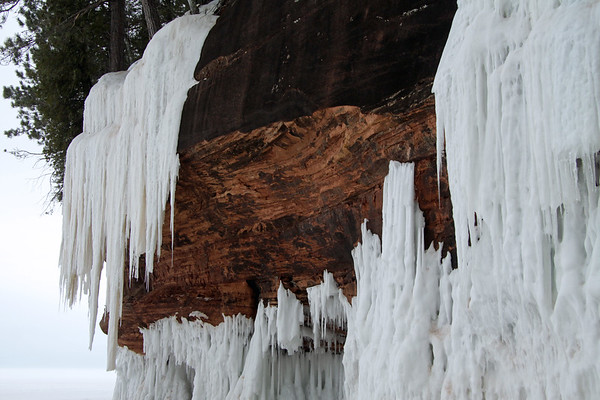 Wave ice meets stream/waterfall ice - with the iron oxide rich sedimentary sandstone between.