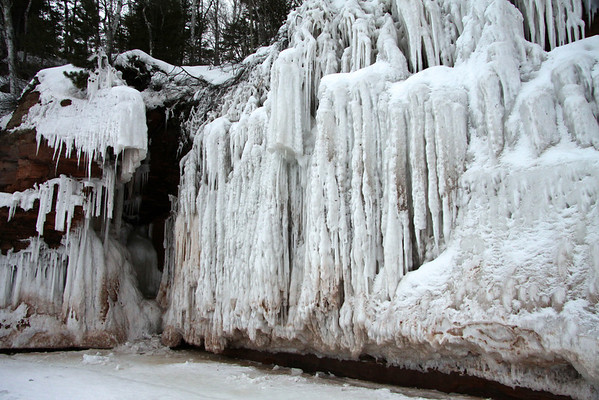 Sea cave along Lake Superior - with several fallen icicle fragments upon the lake.