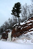 """White Pine along the sandstone ridge - with the frozen waterfall and ice column - along the """"Bowl"""" area of the Bayfield Peninsula."""