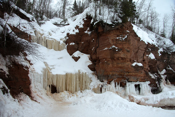 Late fall season stream flowing from the sandstone lake cliff, forms the ice sculpted waterfall along the frozen waves of Lake Superior - with the sea/ice cave behind.