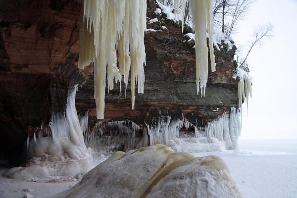 Mid-winter season ice sculpting along the sedimentary sandstone rock cliff shoreline of Lake Superior.