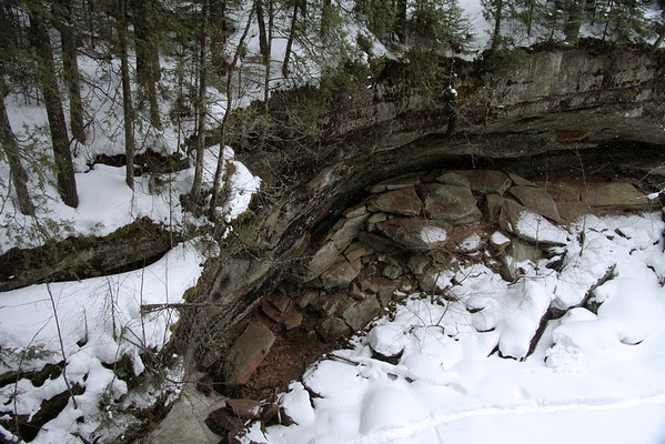 Twin Falls - sourced by Larson Creek - Bayfield (county) - pines along the snow cloaked rock ledge, with fallen eroded sandstone boulders below.