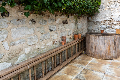 Europe, France, Giverny.  Ladder and pots against a stone wall.