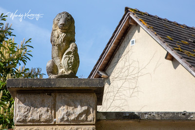 Europe, France, Giverny.  Stone lion and gable.