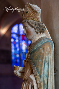 Europe, France, Giverny.  Stone statue of  Saint Louis d'Anjou in profile against a stained glass window.