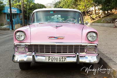 Cuba, Havana.  Front end view of a classic car parked along a city street.