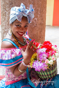 Cuba, Havana, Old Havana.  Woman in traditional dress holding flowers and a cigar.