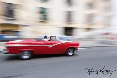 Cuba, Havana, Old Havana.  Red, classic convertible in motion.