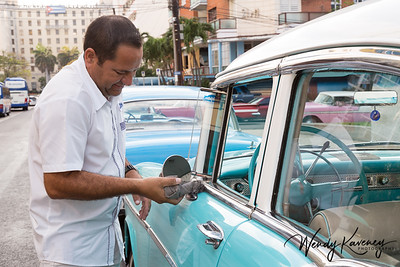 Cuba, Havana.  Man polishing his teal classic car.