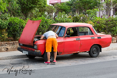 Cuba, Havana.  A man in bright orange shorts bends over the engine of his bright red car.