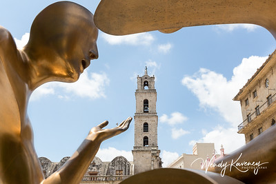 "Cuba, Havana, Old Havana.  The tower of Basílica Menor de San Francisco de Asís framed by a contemporary bronze statue called ""'La Conversación'' in Plaza San Francisco."
