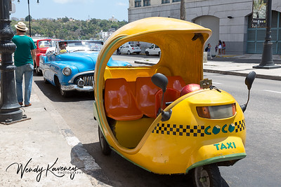 Cuba, Havana, Old Havana.  Cocotaxi and classic cars parked along the street.