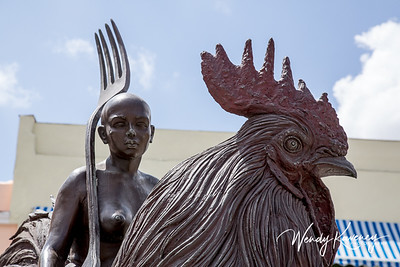 Cuba, Havana, Old Havana.  Close view of a bronze statue of a woman on a rooster holding a fork in Plaza Vieja. (Old Square)