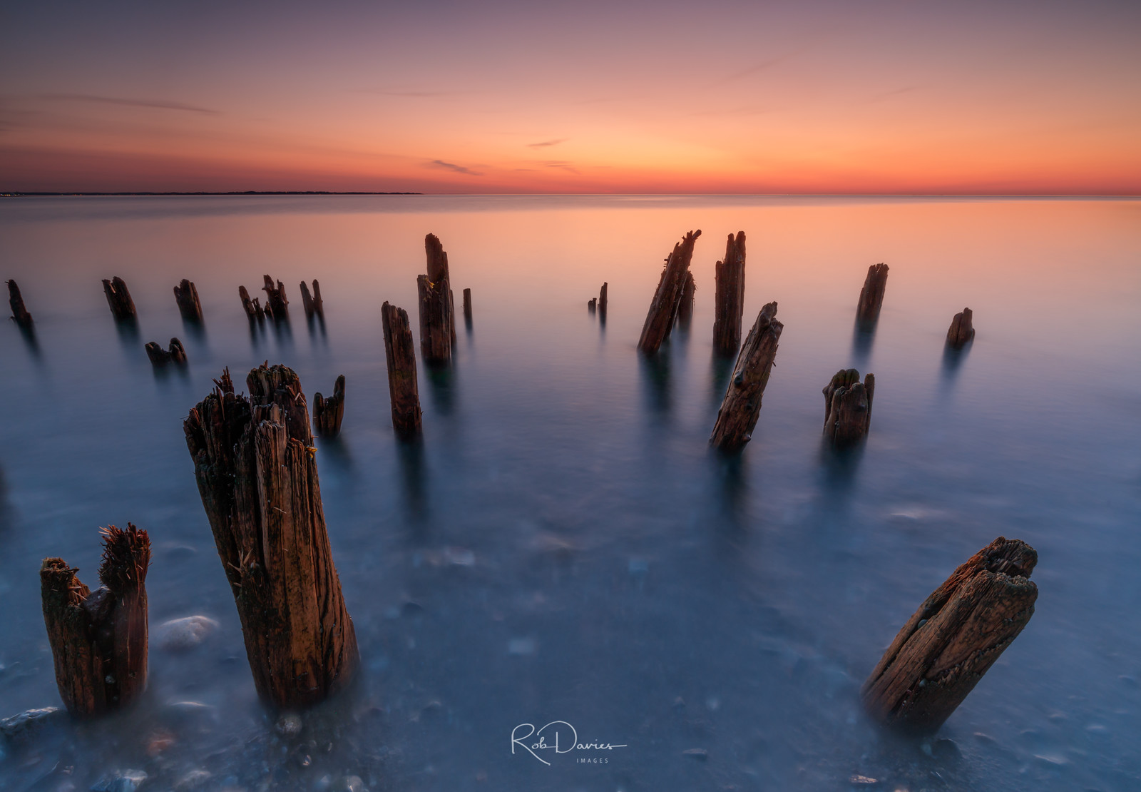 Misty ocean surrounding wooden posts at sunset