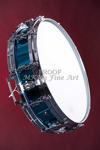 A blue finish snare drum isolated against a dark red background in the vertical format.