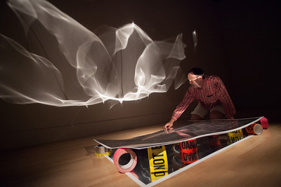 """Light is reflected off of the mirrored paper which creates a pattern of light on the gallery wall. Rolls of tape such as """"Danger"""", """"No Trespassing"""", """"Caution Do Not Enter"""", and pink duct tape act as kinds of pedestals for the paper.  Charles Matson Lume received a M.F.A. and M.A. from the University of Wisconsin-Madison and a B.A. in Psychology from Wheaton College, Wheaton, IL. His art has been exhibited at institutions such as: the Irish Museum of Modern Art, (Dublin, Ireland), Babel Kunst (Trondheim, Norway), Hunter College, (NYC), Minnesota Museum of American Art (MN). Charles has received fellowships from the Bush Foundation, Jerome Foundation, and the Minnesota State Arts Board. Charles is a Professor of Art at the University of Wisconsin-Stout where he teaches painting, drawing, and aesthetics. He lives with his wife, Sarah, and daughters, in St. Paul, MN."""
