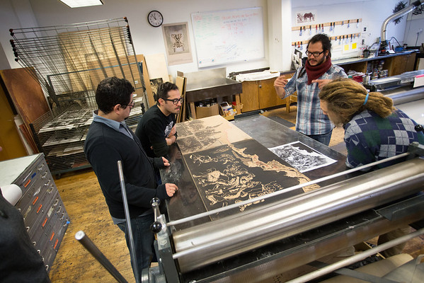 Salvador Jiménez Flores (2nd from right, Pulso curator and KCAD Outreach/Multicultural Admissions Counselor) critiquing a printmaking student's work.