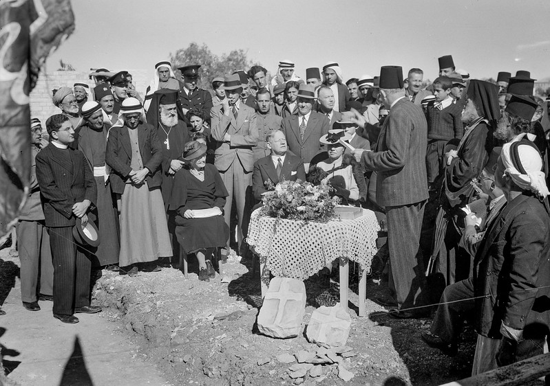 Laying of corner stone for municipal school by District Commissioner Keith Roach. Address by Mayor of Ramallah Salem el-Zaahour with natural cross found in stone in foreground. 1940