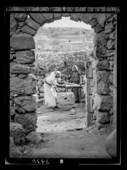 Olive crushing and pressing. Process of applying the weight. Scene framed by ancient archway showing village.  1920-1933