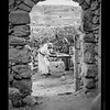53.  Olive crushing and pressing.  Process of applying the weight.  Scene framed by ancient archway showing village. 1920–1933