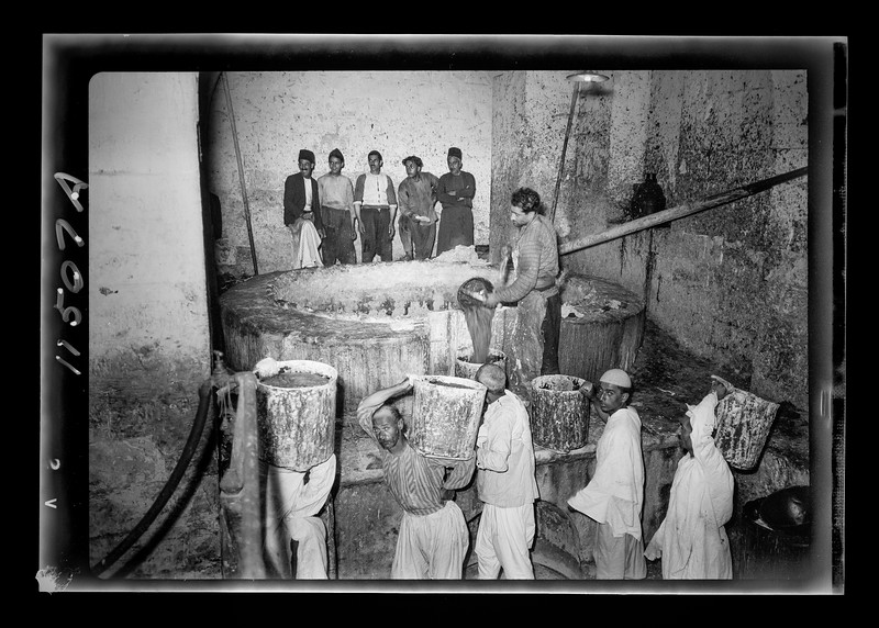 Nablus soap factory.  The boiling pot liquid soap being carried to the stock room.  1940