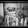 45.  Nablus soap factory.  The boiling pot liquid soap being carried to the stock room. 1940