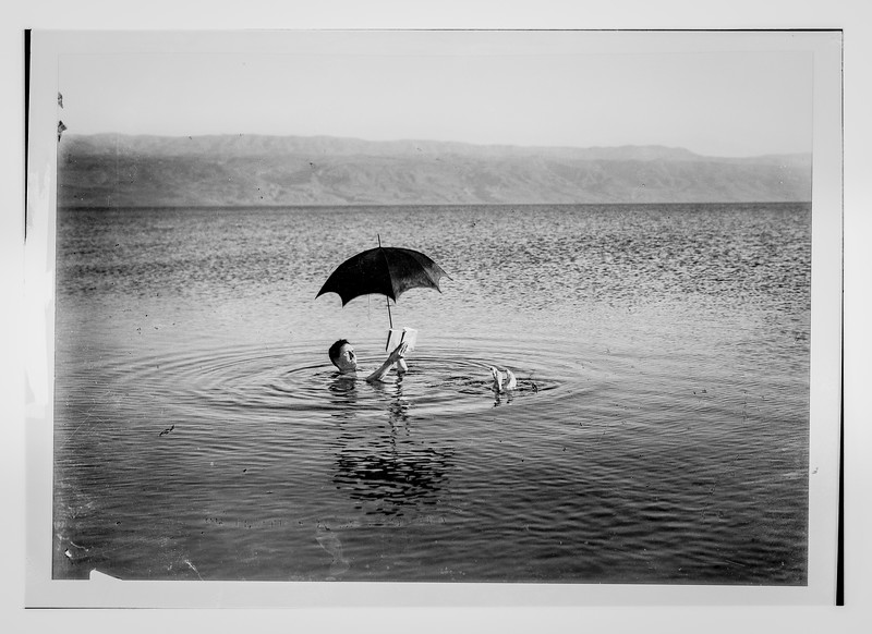 The Dead Sea. Man floating with book and umbrella in his hands.  1900-1920