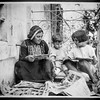 Arab woman in traditional dress, seated with boy and girl, looking at comics.  1920-1935