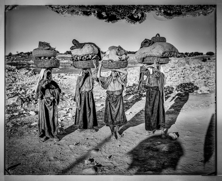 Four Palestinian women on their way to market with baskets on heads. 1898-1946