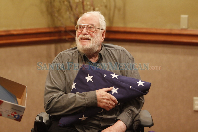 Michael P. E. Hoyt, 86, holds a flag that flew over the US Capitol that was presented to him by Bobbie Ferrell, with senator Tom Udall's office, on Thursday, August 25, 2016. Hoyt is a former State Department employees who was captured and held hostage with his staff in 1964 by Congolese Simba rebels. Luis Sánchez Saturno/The New Mexican