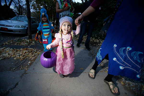 Lisa Anderson, walks her daughter Ila Benson, 2, as Rapunzel, on Don Gaspar Ave. while trick or treating for Halloween in Santa Fe on Monday, October 31, 2016. Luis Sanchez Saturno/The New Mexican