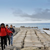 Three people on the sea wall at the Ponta do Sol coastline on the island of Madeira - a color image