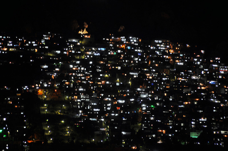Nighttime over Damascus neighborhood built on steep mountain flank, Syria