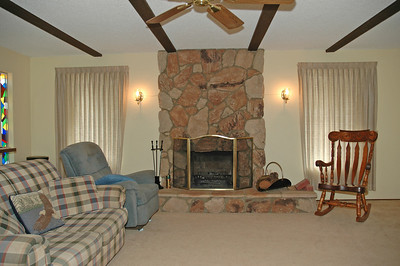 Large family room with a wood burning fireplace. Framed by two wall sconces.