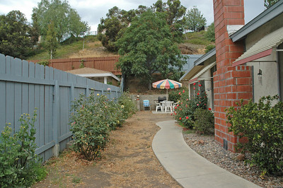 The side yard located on the South side of the property offers a concrete sidewalk from the gate to the back patio door. Rose bushes galore!