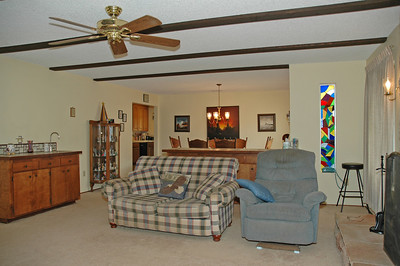 The family room is open to the dining room and has a wet bar and ceiling fan.