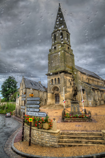 The Rainy Church<br /> For the two weeks we were in Europe, it only rained hard one day. Even then, most of that time we were returning from Normandy, back to Paris. Traveling through the French countryside, I could have napped (I could have used it too), but it was so pretty that I didn't want to miss any of it. Each small village would have a church that would be the tallest and oldest building. You could see the steeple above the trees and roof tops as you entered and it was always on the main street through town. Trying not to fall asleep, I took this photo through the coach window as we passed through Creully, Lower Normandy, France.