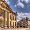 The Clarendon Building<br /> The Clarendon Building (on the left) is a landmark building in Oxford, England, owned by the University of Oxford. Built between 1711 and 1715 , it stands in the center of the city in Broad Street, near the Bodleian Library and the Sheldonian Theatre. From what I can tell from other online photos, this may actually be the back of the building. We didn't have an opportunity to walk around, but I was pretty impressed with the side I saw.