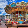 The Honfleur Carousel<br /> By the entrance to the little marina in Honfleur, France is this beautiful, double decker carousel. I haven't found much information online about it, other than it's open during the tourist season and possibly built around 1900. It wasn't crowded the day we stopped by and no one went to the second level, but the teenagers in our group regressed a few years as they enjoyed it. In a way the carousel symbolizes Honfleur, because though it may be old, it is colorful, happy and on the move. Honfleur bustles with activity as tourists walk, shop, eat and just enjoy the beauty of this town.