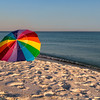 Rainbow on the Beach<br /> Walking along Pensacola Beach, I saw this lonely beach umbrella waiting for someone to come visit. Fortunately, the wind wasn't heavy or it might have taken a trip of its own down the shore.