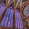 The Stained Glass of La Sainte-Chapelle<br /> It was a busy day. We had just left Notre Dame de Paris and was suppose to go straight to the Louvre, but Kathy, our fearless leader had penciled in a stop at La Sainte-Chapelle. This side trip cut our time at museum considerably, but it was definitely worth the effort. <br /> <br /> At first you enter a low ceiling chapel and though very nice, you wonder what all the fuss is about. But at the back corners are tight winding stairs that spiral to the second story, where the ceiling rises much higher than expected. Though one wall was covered (due to maintenance I'm guessing) the view was incredible. The detail and size of the windows are hard to imagine until you see it in person. This is some of the best in the world.