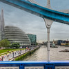 The View from Tower Bridge<br /> Driving across Tower Bridge affords you a view of the old and new London has to offer. The WWII ship, the HMS Belfast is moored on the south bank of the Thames alongside a uniquely shaped building that houses City Hall. The tall skyscraper in the distance is the Shard. Standing 1,016 feet high, it opened on July 5, 2012 during our trip and is now the tallest completed building in Europe. The Olympic rings had just gone up on Tower Bridge the night before we first saw it, but only seeing it from a moving tour bus did not afford me a great view from which to photograph it.