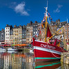 Honfleur, France<br /> Leaving the Normandy countryside in northwestern France, our tour group stopped at small fishing town on the Seine called Honfleur, close to the Pont de Normandie.. Full of the flavor of France, this town is a photographer's dream. Known for its old, beautiful picturesque port, the colors and shapes of small shops and cafes contrast against old historic churches and the many boats in the harbor. The weather was perfect the day we visited and we had time to wonder about. It was one of the few stops where we could relax and soak in the local ambiance, truly feeling like we were indeed in France.