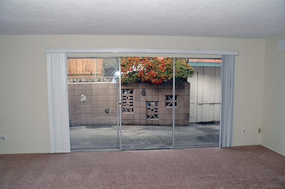 A large sliding glass door leads to a private patio.